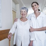 Shot of a beautiful young nurse walking with an elderly patient in hospital